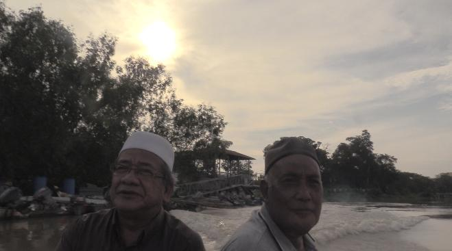 Ustaz Wahab and the ferry man taking us on a ride along the (CHECK) Teluk Intan river.