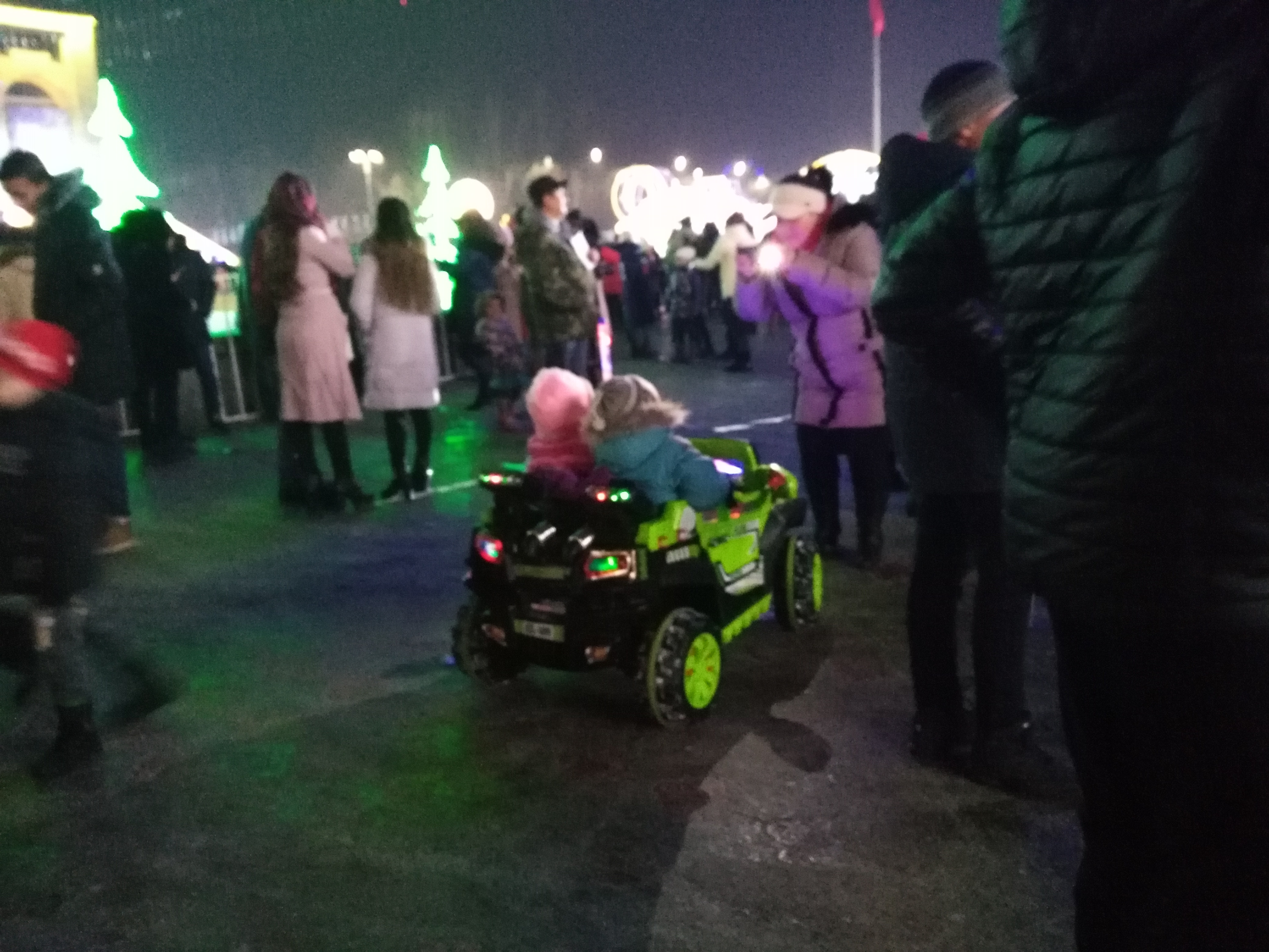Puny babies riding in cars propelled by remote controls controlled by their guardians at the Ala-Too Square during New Year's eve.