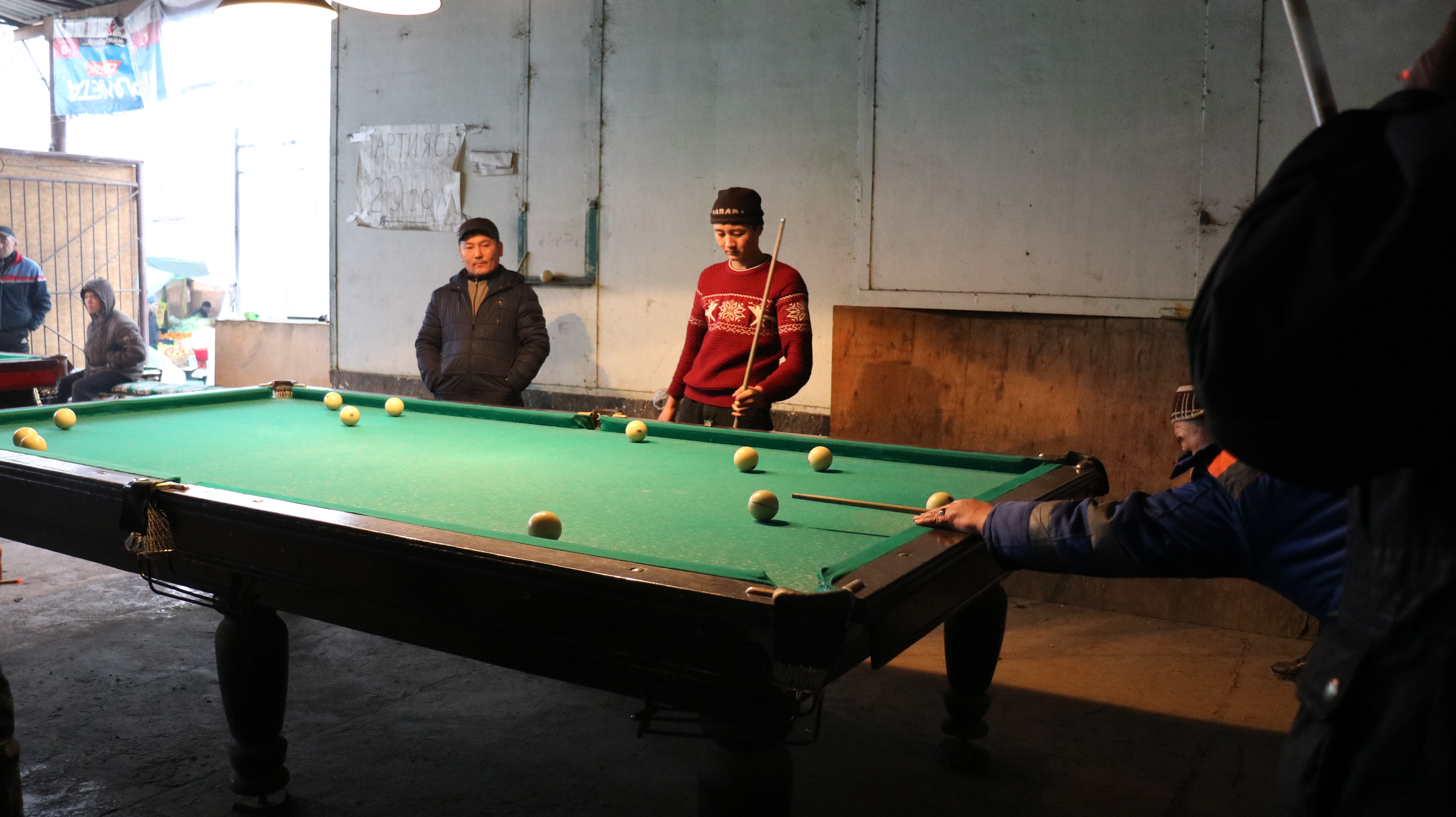 People casually playing pool at the Bazar.