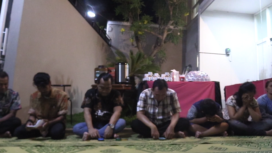 Neighborhood members bowing their heads during the Islamic blessing of the night.